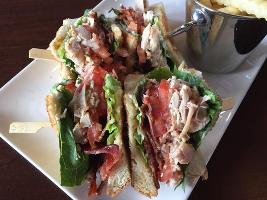 At Redwood Rotisserie & Grill, the Saratoga club sandwich assembles a classic figure: pulled chicken, bacon, lettuce, tomato, swipes of mayo, white toast.