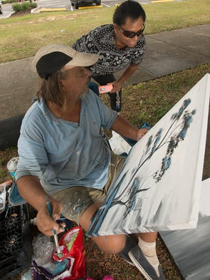 Laura Lee, right, gets a better look at homeless artist,
