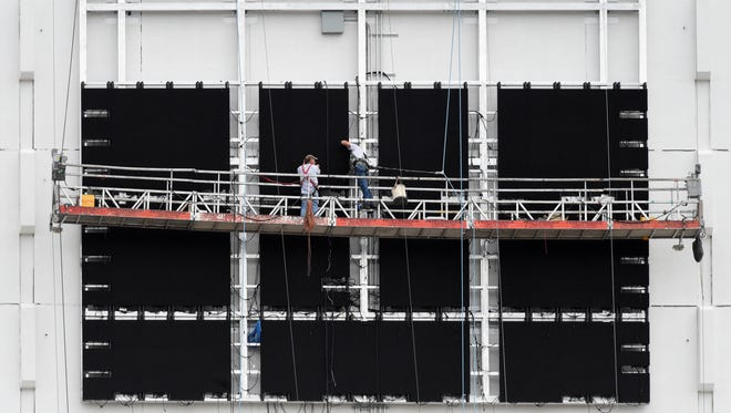 Workers install a Jumbotron on the west side of Grand Sierra Resort and Casino on July 8, 2014.