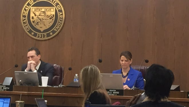 Sen. Steve Smith, R-Maricopa, and Sen. Kelli Ward, R-Lake Havasu listen as the public responds to a bill that would keep secret for 3 months the names of officers involved in police shootings on Feb. 11, 2015.