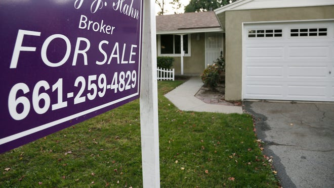 FILE - This Monday, Nov. 3, 2014, file photo, shows a house for sale in Los Angeles.  Buying a new home while trying to sell your current one can leave you short of money, or even struggling to carry two mortgages. But there are strategies that can help free up cash to make it work.