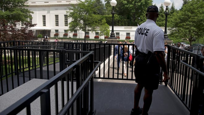 A member of the Secret Service Police looks toward the West Wing of the White House in Washington on June 9, 2015, during an evacuation of the media area of the White House due to a bomb threat. No bomb was found.