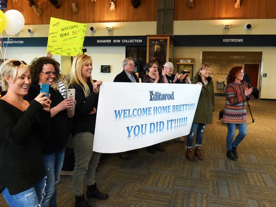 Suzette Bruggeman, far right, joined by family, friends and fans greet her husband Brett at the Great Falls International Airport, Monday.  Brett Bruggeman returned from Alaska where he competed in the Iditarod sled dog race, which he finished in 39th place as a first time competitor in the iconic race.