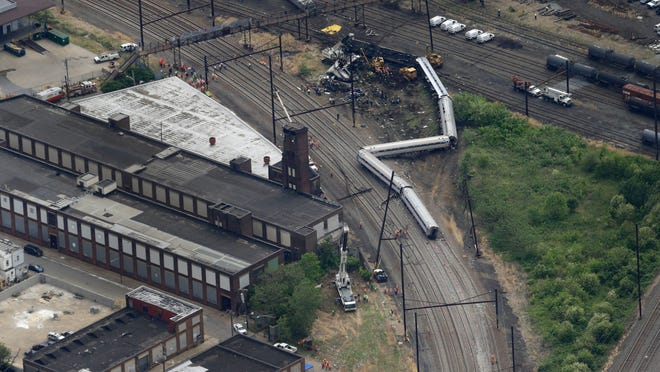 In this aerial photo, emergency personnel work at the scene of a passenger train wreck in Philadelphia on Wednesday, May 13, 2015. Federal investigators arrived Wednesday to determine why an Amtrak train jumped the tracks in Tuesday night's fatal accident. (AP Photo/Patrick Semansky)