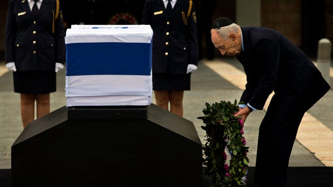 Israel's President Shimon Peres lays a wreath next to the coffin of Israeli Prime Minister Ariel Sharon at the Knesset Plaza in Jerusalem on Sunday.
