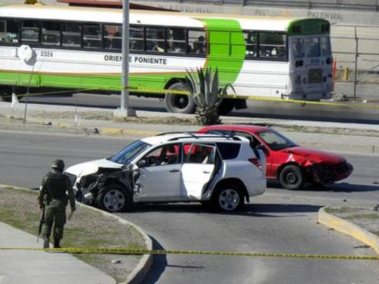 A soldier stands guard at a crime scene in March 2010 where the crashed car of a U.S. Consulate employee sits near the Santa Fe Bridge in Juárez. The U.S. Consulate employee and her husband were shot to death in their car, where their baby was found crying but unharmed in the back seat.