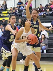 Alamogordo's Breyanna Bickham tries to score in the paint while being heavily guarded.