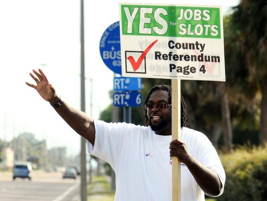Jabari Wash, outside the Cocoa-Rockledge Garden Club, encourages people to vote for the referendum on slots.
