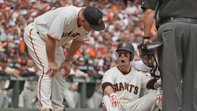 Giants manager Bruce Bochy, left, checks Buster Posey on the ground after he was hit by a Taijuan Walker pitch in the first inning of Monday's game.
