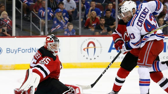 New Jersey Devils goalie Cory Schneider (35) kicks the puck away as teammate defenseman John Moore battles Rangers center Daniel Catenacci (43) during the first period of a preseason NHL hockey game in Newark on Saturday, Sept. 23, 2017.