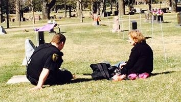 A Watertwon police officer comforts a grieving mother.