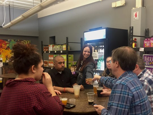 Andrea Whaley, the office manager at River Horse Brewing Company, passes out Caramel DeLights to customers in the taproom.