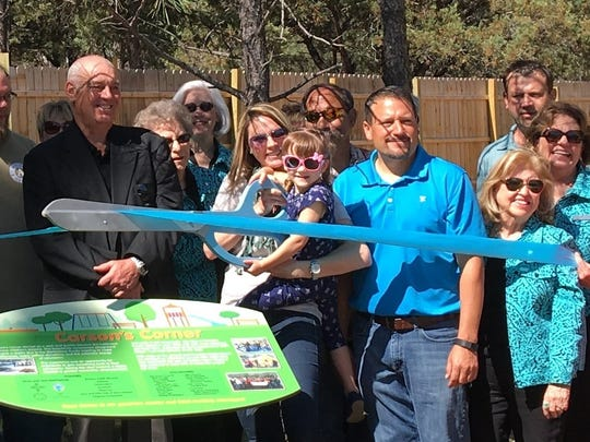 Held by her mother, Carson Stettheimer flashes a smile while clamping down on the ribbon, At right is Village Parks and Recreation Director Rodney Griego and at left is Robert Donaldson representing the Hubbard Foundation.
