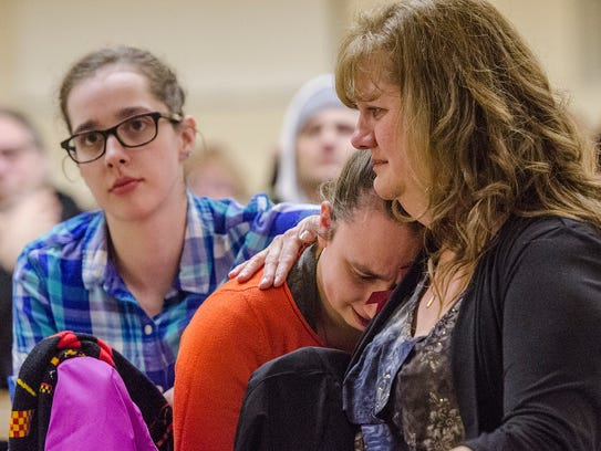 Ann Stislicki comforts her daughters during a vigil in Redford.