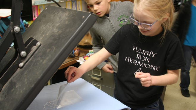 Scarlette Leiterman uses the heat press to finish her own shirt, something Technology and Manufacturing Club students get to do once they've done projects for clients.