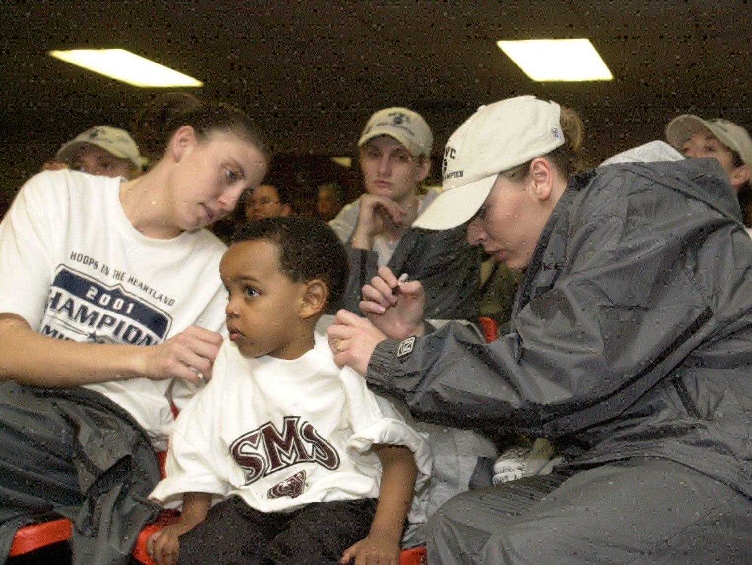 Jackie Stiles, right, signs autograph for Niekie Thomas, then 2, while teammate Carly Deer looks on during a watch party for NCAA Tournament seeding in 2001.