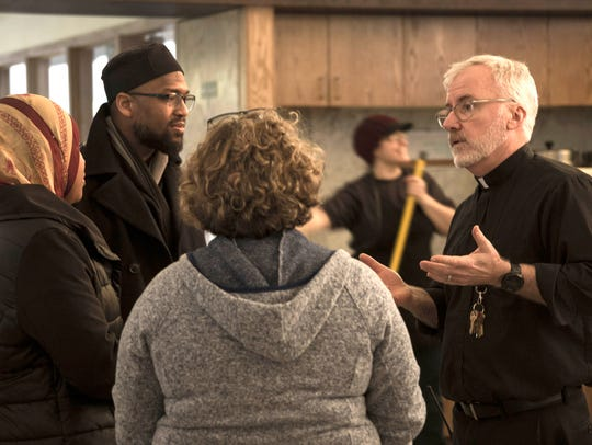 Father Tim McCabe SJ., right, speaks with members of