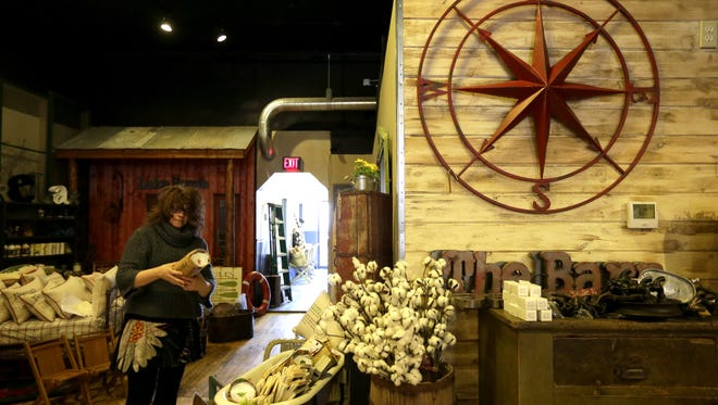 Owner Tina Palmer puts new items on display at Red Door Mercantile in downtown Neenah.
