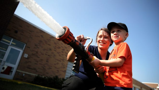 Jessie Minehan, in Fox Valley Technical College's Law Enforcement 720 Academy, helps Maverick Thurs, 3, of Hortonville, spray a firehose during FVTC's Public Safety Day Saturday in Greenville.
