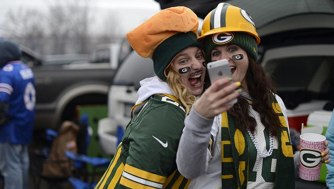 Ashley DeGolier of Bradford, Pa., left, and her cousin Lindsey Barr from Charlotte, N.C., mug for a selfie while tailgating before the game. The two grew up Green Bay Packers fans thanks to their grandfather. At left, Ashley DeGolier of Bradford, Penn., and her cousin Lindsey Barr, from Charlette, N.C.,  have some fun taking a selfie while tailgating before a December 2014  Green Bay Packers game at Ralph Wilson Stadium in Orchard Park, N.Y.