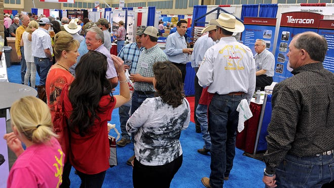 A group of people talk in front of a row of vendor booths during the 2014 Texas Alliance of Energy Producers Expo Oil Patch Reception at the Multi-Purpose Events Center.