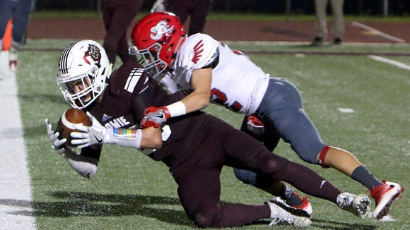 Bowie's Dustin VanWey (left) falls into the end zone for a touchdown after making a catch over Holliday's Chase Borchardt (22) Friday night at Bowie.