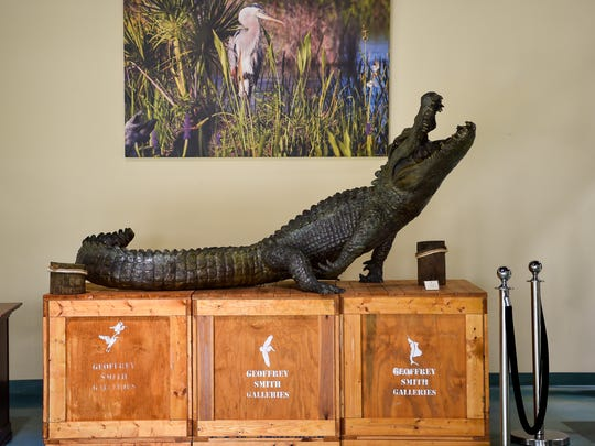 "Sculptor Geoffrey Smith's ""Everglades Gator"" is seen July 27, 2017, near one of his photographs at his studio and gallery at 4545 SE Dixie Highway in south Stuart."