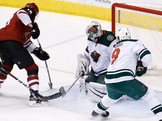 Arizona Coyotes center Christian Dvorak (18) scores a goal against Minnesota Wild goaltender Alex Stalock, second from right, as center Mikko Koivu (9) watches during the third period of an NHL hockey game Thursday, March 1, 2018, in Glendale, Ariz. The Coyotes defeated the Wild 5-3. (AP Photo/Ross D. Franklin)