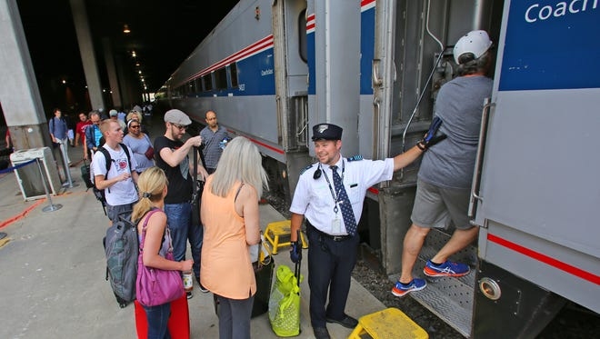 Amtrak conductor Ben Bertrand helps people board an Amtrak train at the Amtrak Intermodal Station on St Paul and 4th St. in Milwaukee on Tuesday, July 28, 2015.