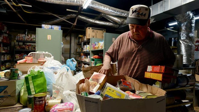 Patrick Prato, a volunteer at the HALO Center of Hope in Salisbury, sorts donated food items Monday morning.
