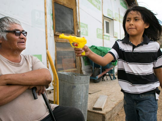Peterson Bell, 58, who has diabetes, arthritis and vision impairment, looks on as his grandson, Kravin Keyanna, 8, plays with a water gun at their home, which is surrounded by abandoned uranium mines in Church Rock, N.M., on the Navajo Reservation. Bell worked these uranium mines from 1974 through 1982. Bell's exposure to uranium could likely be responsible for his health issues.