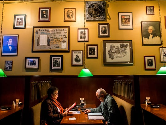 Veronica and Oliver Durham sit in a booth at Dead Presidents