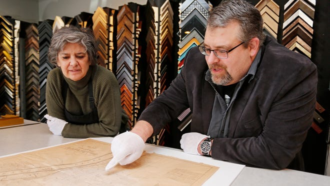 Colby Bartlett points out key features as he and Janie Peters look over a copy of the first map printed of Lafayette Monday, March 19, 2018, at Art of Framing, 2505 S. Earl Avenue in Lafayette. The map was printed in 1841 by C. Bartlett's Lithography in New York City.
