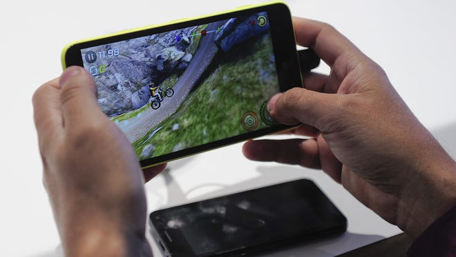 A visitor plays game on a Nokia device during the 2014 Mobile World Congress in Barcelona on February 26, 2014 The Mobile World Congress runs from the 24 to 27 February where participants and visitors alike can attend conferences, network, discover cutting-edge products and technologies at among the 1,700 exhibitors as well as seek industry opportunities and make deals.  AFP PHOTO / JOSEP LAGOJOSEP LAGO/AFP/Getty Images ORG XMIT: - ORIG FILE ID: 527507120