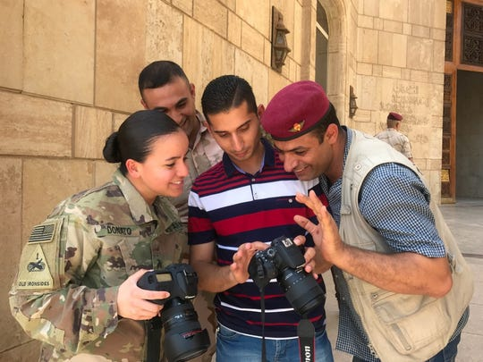Sgt. Von Marie Donato, left, a public affairs NCO with the 1st Armored Division, provides media and photography training to Iraqi security forces and media personnel in Baghdad. The 1st Armored Division headquarters is deployed in Iraq in a mission command role.