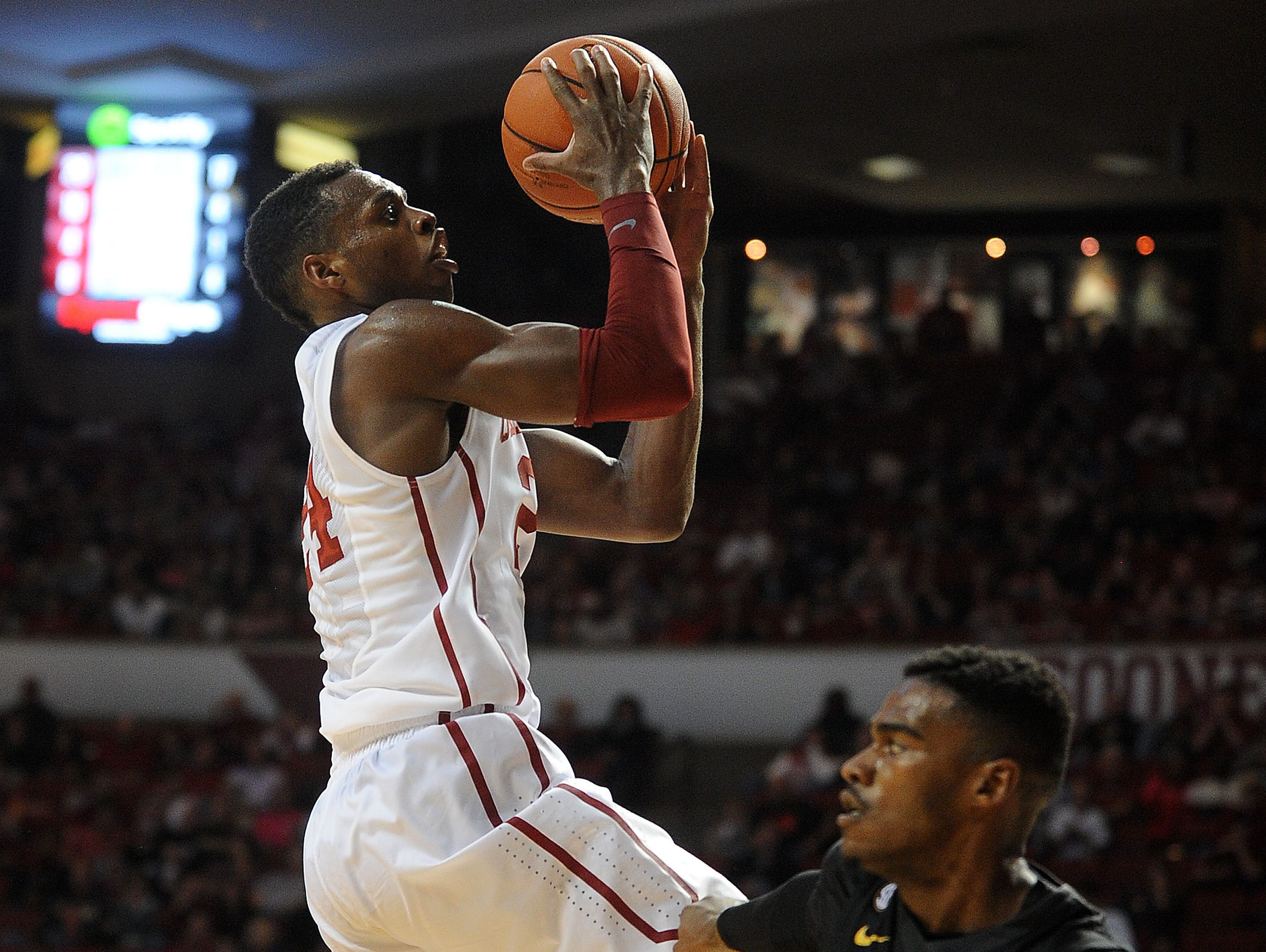 Oklahoma Sooners guard Buddy Hield (24) attempts a shot around Missouri Tigers guard Keith Shamburger (14) during the second half at Lloyd Noble Center in Norman, Okla. on Friday.