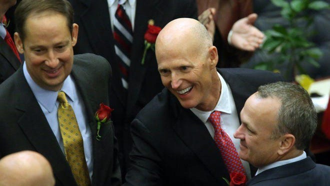 Gov. Rick Scott flanked by Sen. Joe Negron, R-Stuart, (left) and Rep. Richard Corcoran, R-Land O' Lakes, makes his way to the podium to deliver his State of the State address.