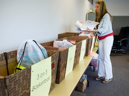 Jennifer Wucherer, St. Cloud Aging Services Department, prepares bins for staff at each event of the Minnesota Senior Games on Wednesday, May 18, 2016, at the Whitney Senior Center.