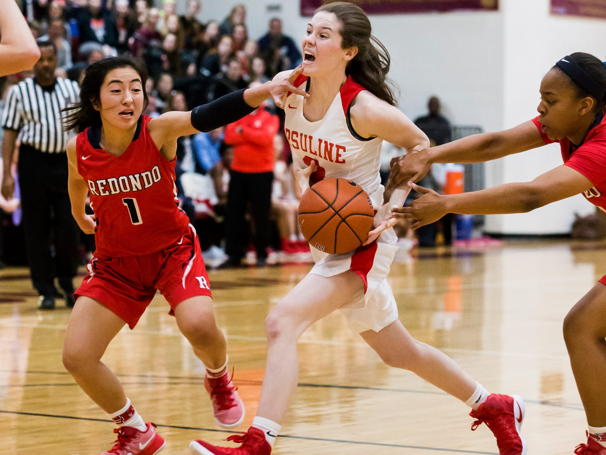 Ursuline's Magie Connolly is fouled as she cuts to the basket through a pair of Redondo Union defenders in the first half of Ursuline's 39-26 win over Redondo Union High School in the Diamond State Classic at St. Elizabeth High School in Wilmington on Tuesday night.