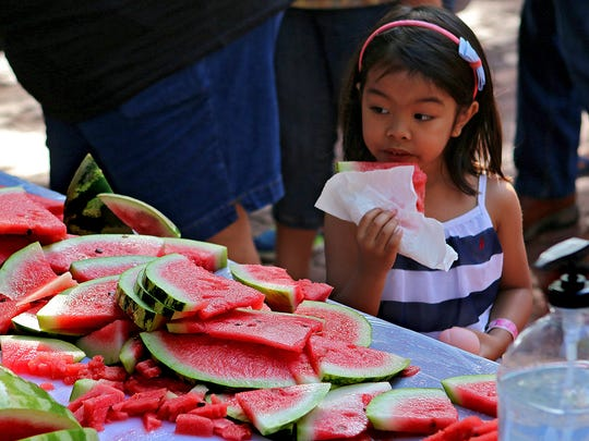 A young girl enjoys a watermelon slice during the Downtown Wichita Falls Farmers Market's annual Watermelon Fest Saturday morning.