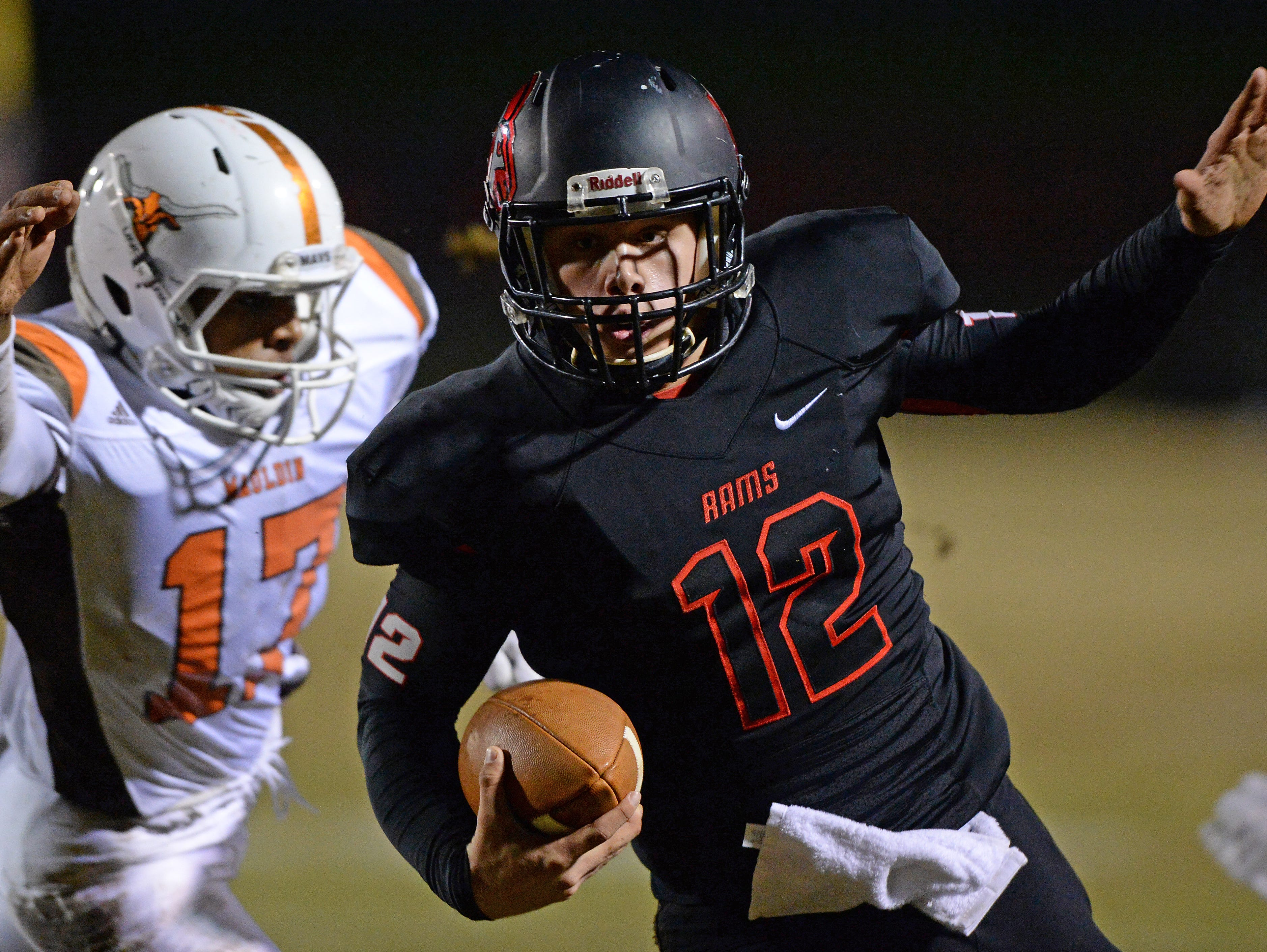 Hillcrest quarterback Collin Sneed (12) carries past Mauldin's Charles Gupton (17) during the first round of the Class AAAA Division-I playoffs Friday, November 20, 2015 at Hillcrest High.