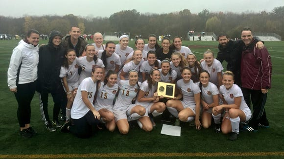 Arlington's girls soccer team poses with the plaque
