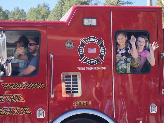 Children waving from Ruidoso Downs Fire Rescue in the