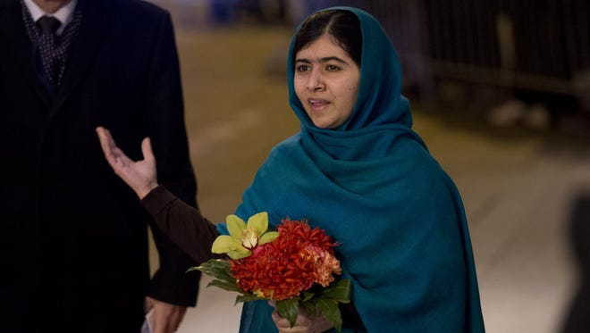 Malala Yousafzai, then 17, briefly speaks to the news media as she arrives at her hotel after flying to Oslo to receive her Nobel Peace Prize award in 2014.