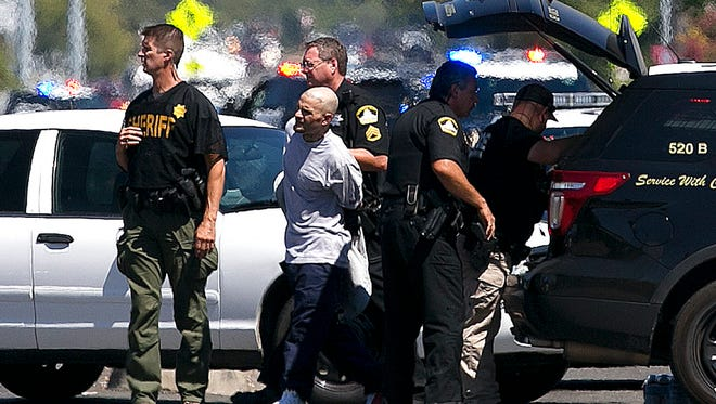 A suspect believed to be involved in the shooting of law enforcement officers is taken from the scene by Sacramento County Sheriff's Deputies, Wednesday, Aug. 30, 2017, in Sacramento, Calif.
