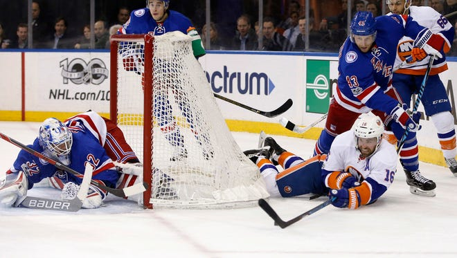 Rangers defenseman Steven Kampfer (43) defends as Islanders left wing Andrew Ladd (16) tries to get to the puck while goalie Antti Raanta defends the goal during the first period of a game at Madison Square Garden in New York, Wednesday, March 22, 2017.
