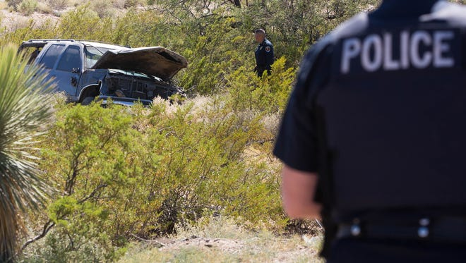 Las Cruces Police officers investigating the scene of a rollover near Highlands Elementary School. Monday September 25, 2017.