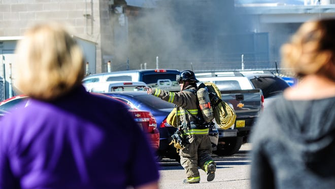 A firefighter motions to another on Tuesday while arriving on the scene of a structure fire at the Olam Factory, located on West Amador Avenue.