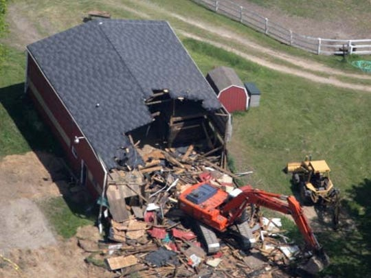 Federal agents in their continuing search for Jimmy Hoffa's body, tear down this barn Wednesday, May 24, 2006, on the Hidden Dreams Farm in Milford, once owned by a Hoffa associate.