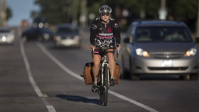 A cyclist navigates the morning commute in the bike lane on Ingersoll Avenue in Des Moines on Tuesday.
